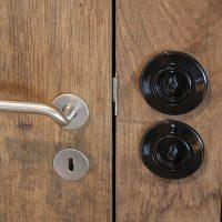 Zimmertüren aus altem Eichenholz mit schlichten Türbeschlägen aus Edelstahl und historisch anmutenden Lichtschaltern