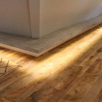 Indirekte Beleuchtung lässt Farbe und Maserung des Altholzes ganz besonders zur Geltung kommen.