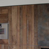 Die rustikalen Küchenfronten sind ebenfalls aus Altholz gefertigt.