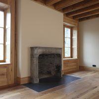 Fensterelemente, Dielenboden und Balkendecke sind aus altem Eichenholz.