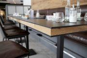 Die eingebetteten Tischplatten aus Altholz ergänzen die Wandverkleidung aus altem Eichenholz