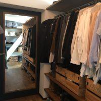 Der begehbare Kleiderschrank nimmt das Thema mit den Schrankbrettern aus Altholz ebenfalls auf.