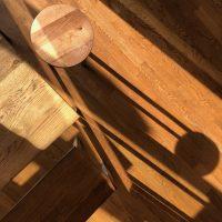 Das alte Eichenholz von Tisch, Hocker, Bank und Dielenboden hat eine lebendige Maserung.