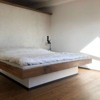 Auch die Bettumrandung nimmt die Verwendung von alter Eiche wieder auf.